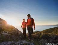 An Hispanic couple is hiking on rocky terrain overlooking the ocean.  The pair are wearing bright orange tops. He is looking back at her and the sun is setting in the background.